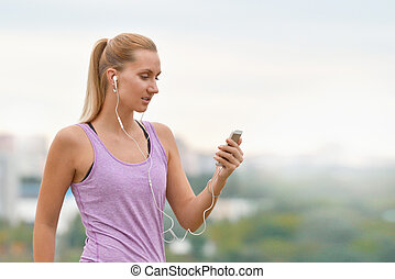 Young female runner is having break and listening to music during the run