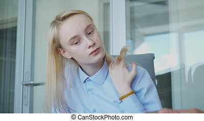Young female secretary touches her blond hair while getting...