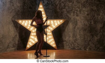 Young female singer with brown curly hair, microphone, dances. shining star in the background. slow motion