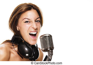 young female singer with headphones and a microphone on white background