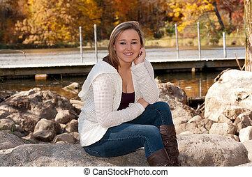 Young Female Sitting on Rock along Lake