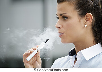 young female smoker smoking e-cigarette outdoors. Head and ...