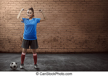 Young female soccer player standing on the alley