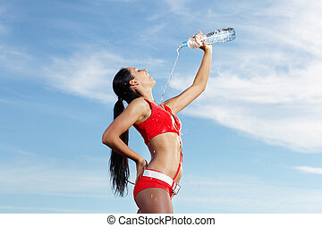 Young female sport girl with a bottle of water