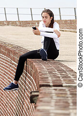 Young female sports woman sitting outside listening to music