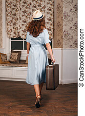 Young female standing in the room with suitcase.