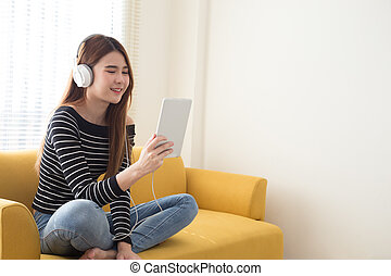 Young female student learning online or reading e-book with headphones and tablet in the room at home, Course online education from website and mobile or making video call concept, Asian thai model