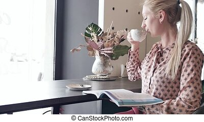 Young female student learns English in a cafe. A pretty blonde is flipping through a magazine and drinking her coffee while sitting at tables in a cafe. Slow motion