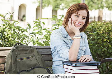 Young Female Student Sitting On Campus with Backpack and Books