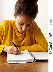 Young female student writing in book