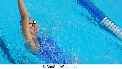 Young female swimmer swimming inside pool. Female swimmer practicing backstroke 4k