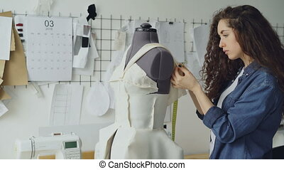 Young female tailor is adjusting clothes on tailoring dummy...