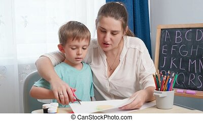 Young female teacher showing her little student how to use scissors. Boy cutting paper with scissors while doing homework