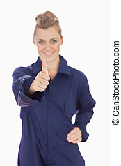 Young female technician gesturing thumbs up