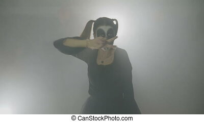 Young female teenager dressed as a sinister doll exercising her zombie dancing moves in fog for halloween night at club