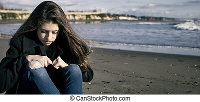 Young female teenager in front of the storm on the beach sad