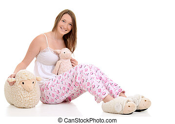 Teenager in pajamas with toy sheep - young female Teenager...