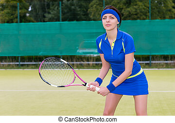 Young female tennis player during the game