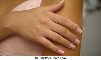 The girl slowly slowly runs her hand over her skin