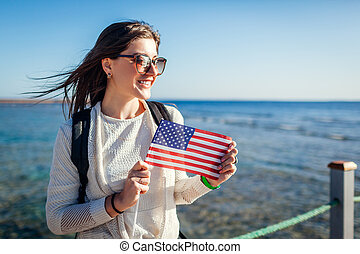 Young female tourist admiring landscape of Red sea and holding USA flag on pier. Independence day of America