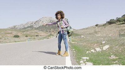Young female tourist hitch hiking - Young woman in casual...