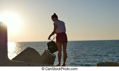 Young female tourist sitting down on the rocks to view the sea. Slow motion. Professional shot in 4K resolution. 101. You can use it e.g. in your commercial video, business, tourism, travel, technology, presentation, broadcast video.