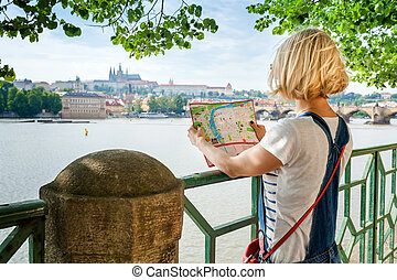 Young female tourist studying a map of Prague.