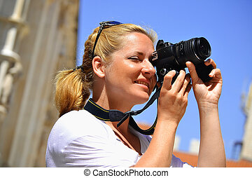Woman taking photos on the street - Young female tourist ...