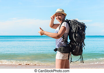 young female tourist with a backpack happy on the beach in Thailand
