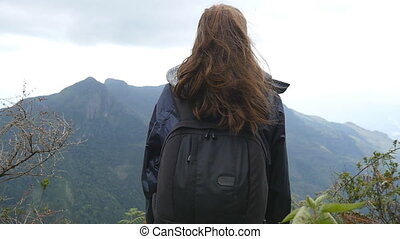Young female tourist with backpack enjoying beautiful view in the mountains. Woman traveler in raincoat standing on the edge of beautiful canyon and looking at nature. Slow motion Rear back view