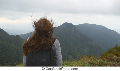 Young female tourist with backpack enjoying beautiful view in the mountains. Woman traveler standing on the edge of beautiful canyon and looking at nature. Slow motion Close up Rear back view