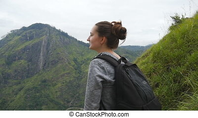 Young female tourist with backpack enjoying beautiful view in the mountains. Woman traveler standing on the edge of beautiful canyon and looking at nature. Slow motion Close up