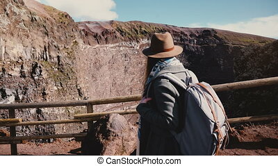 Young female travel blogger with backpack in hat hiking down from Vesuvius volcano, taking photo of the sunny crater. Happy cheerful photographer walking along a mountain road on business trip.