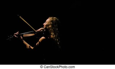 Young female violinist performs a melody of classical instrumental music on the violin. Camera rotates around cute blonde with long hair in dark studio. Close up. Slow motion