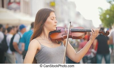 Young female violinist playing a fiddle on pedestrian street...