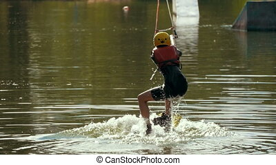 Young female wakeboarding in summer river - slow-motion,...