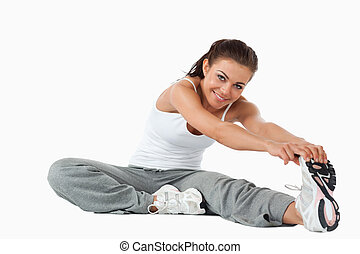 Young female warming up before workout against a white...