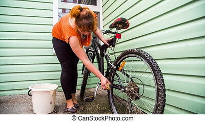 Young Female Washing Bicycle Wheels - This is a process of...