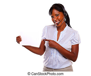 Young female wearing headphones holding white card