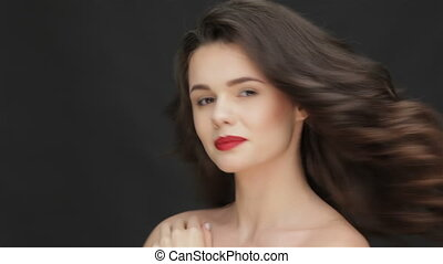 Young female with a charming smile. Portrait of beautiful woman on black background. Beauty Model with Perfect Fresh Skin. Caucasian female model isolated on black background. Perfect fresh skin. Pure beauty model female looking at camera. Beautiful girl touching her face. Caucasian female model ...