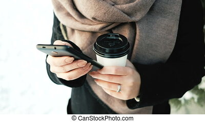 Young female with phone, thermos cup outdoors in winter