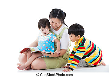 Young female with two little asian children reading a book -...