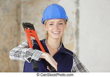 young female worker carrying bolt croppers over her shoulder