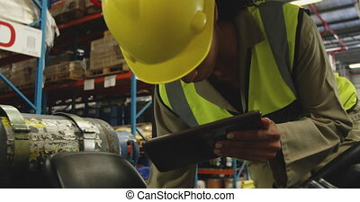 Young female worker driving forklift in a warehouse - Front ...