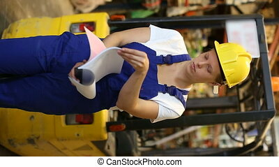 Young female worker holding notebook and looking construction materials at shelves in modern build store