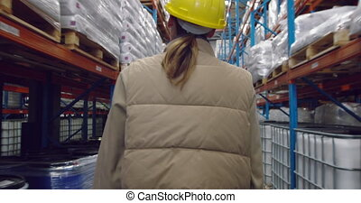 Young female worker walking in a warehouse