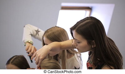 Young females in model school are preparing for lesson.