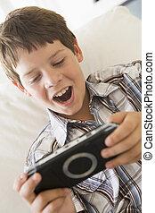 young fiú, noha, handheld, játék, bent