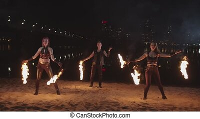Attractive fireshow performers spinning burning poi during dance near river at night. Trio of young poisters performing fire art of spinning and juggling on over night city lights in background.