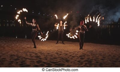 Young fireshow artists juggling flame near river -...